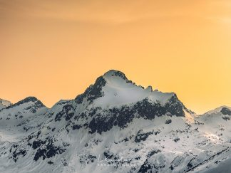 Yellow sky over a snow covered mountain