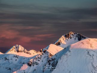 Snow covered mountain peaks at sunset