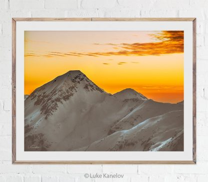 Sunset print over snowy mountain peaks